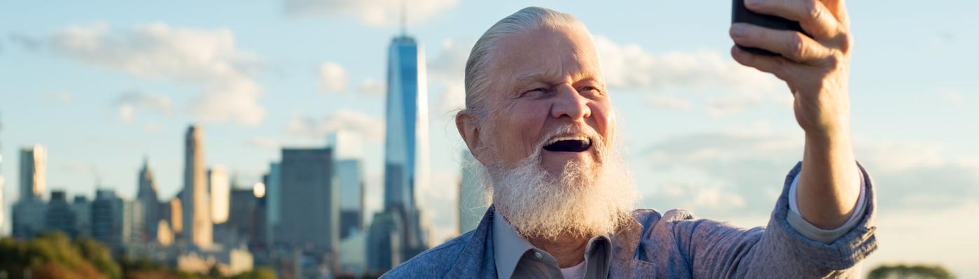 Ein Senior strahlt voller Lebensfreude bei einem Selfie vor der Skyline von New York.